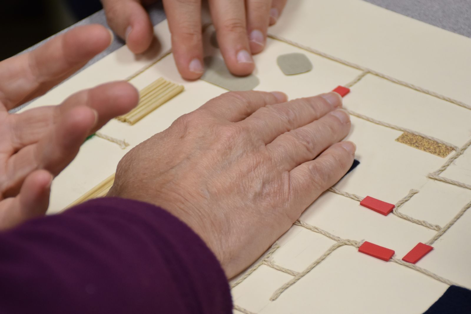 Hands examining a tactile graphic