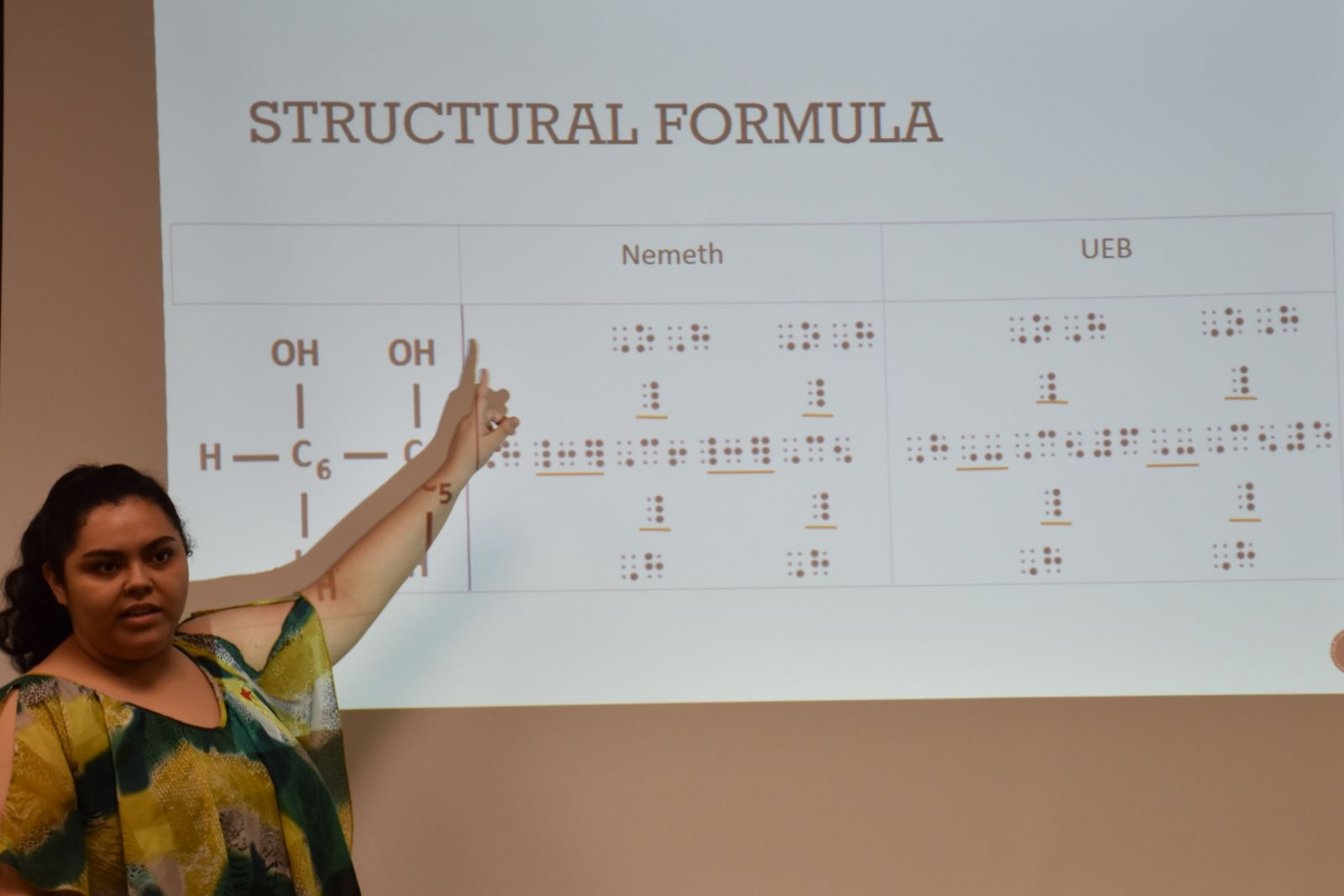 Student presenting on a chemical formula in braille