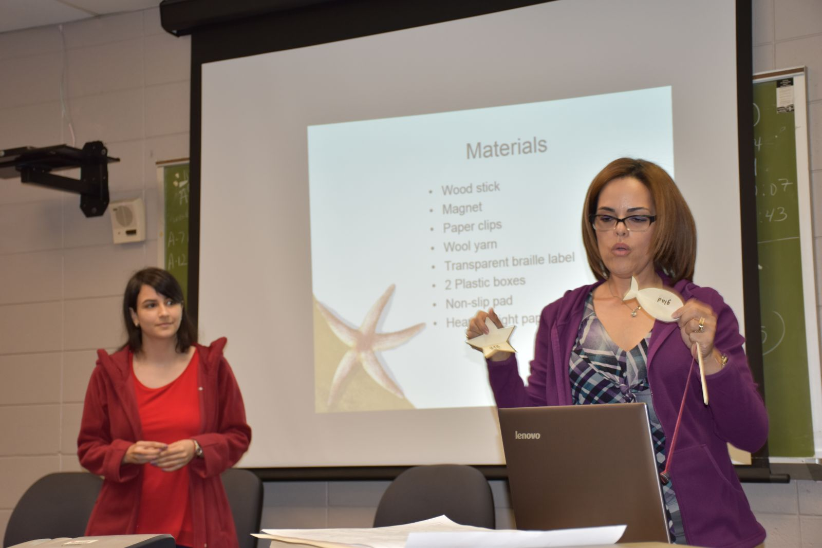 Two women presenting on a game project using a PowerPoint and tactile objects.