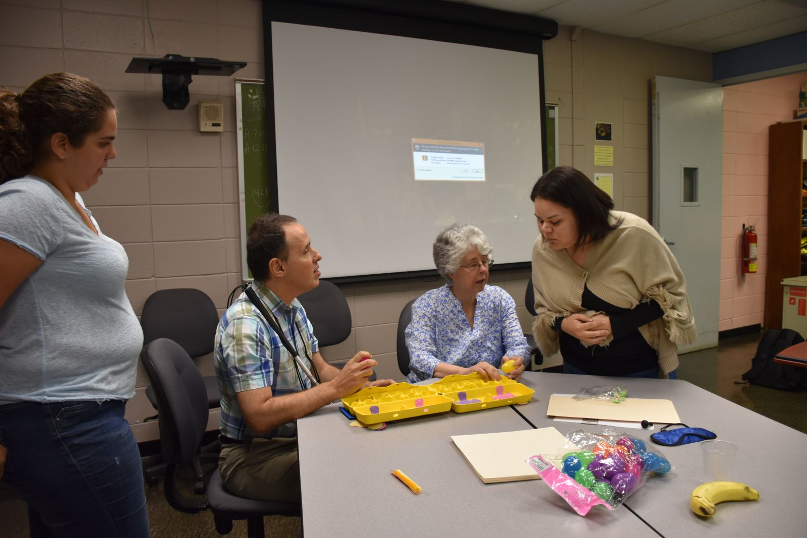 Two women demonstrate a tactile game to two seated instructors.